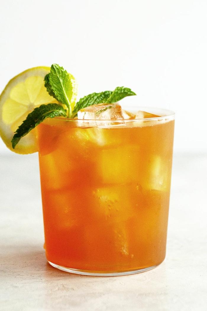 mango eistee selber machen rezept ein glas mit orangem getränk und eiswürfeln und pfefferminze und zitronen