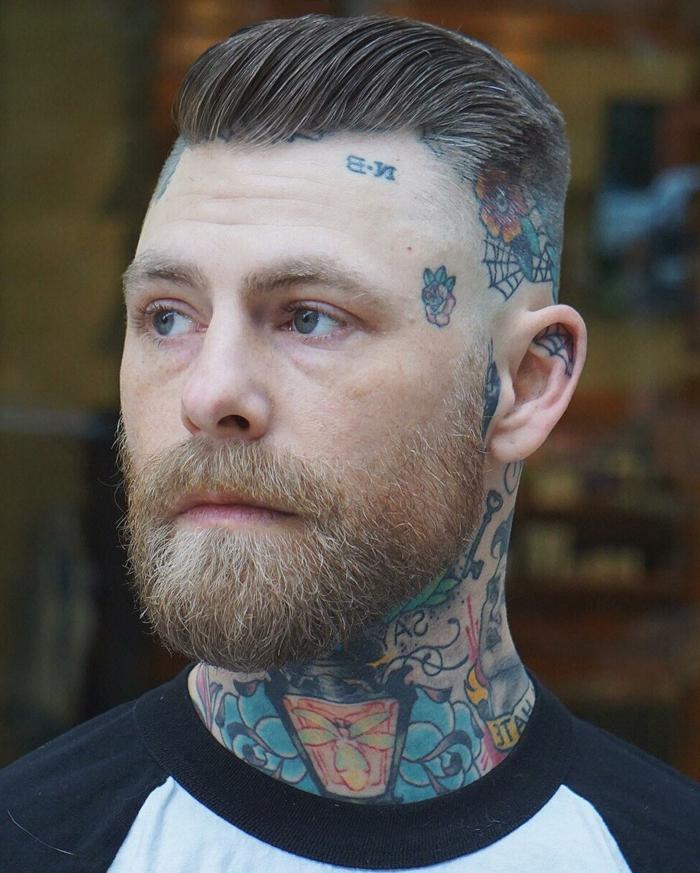 mann mit vielen farbigen tattoos kurzer haarschnitt seiten auf null mit üergang herren kurzhaarfrisuren mit bart dunkelblonde haare