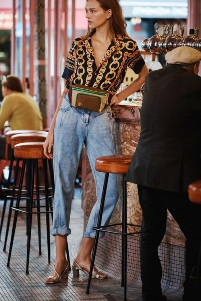 mode fotoshooting cooles modernes outfit hellblaue jeans damen schwarze bluse mit goldenen riemen kleine tasche