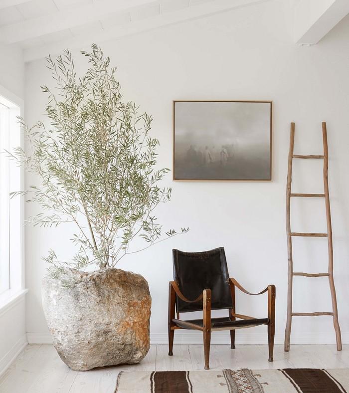 moderne japansische wohnung wohnzimmer japanisch einrichten wabi sabi wohnen japansiches wohnzimmer wabi sabi stuhl aus holz leder schwarz steinvase pflanzen wandbild