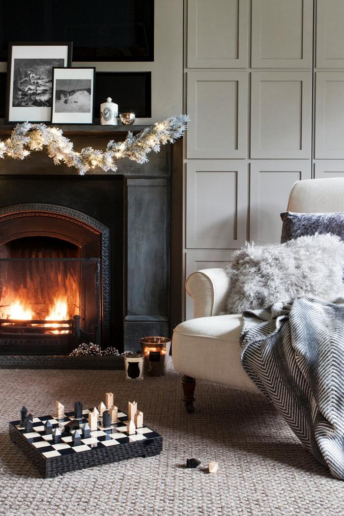 modernes wohnzimmer mit großem kamin weißer sessel hygge style gemütliche inneneinrichtung schwarz weißes schachbrett dekoration