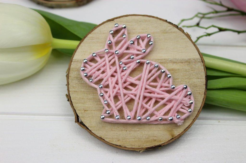 osterhase basteln kleine geschenke zu ostern für erwachsene basteln mit kindern frühling vorlagen osterdeko basteln osterhase aus rosa faden auf holzscheibe