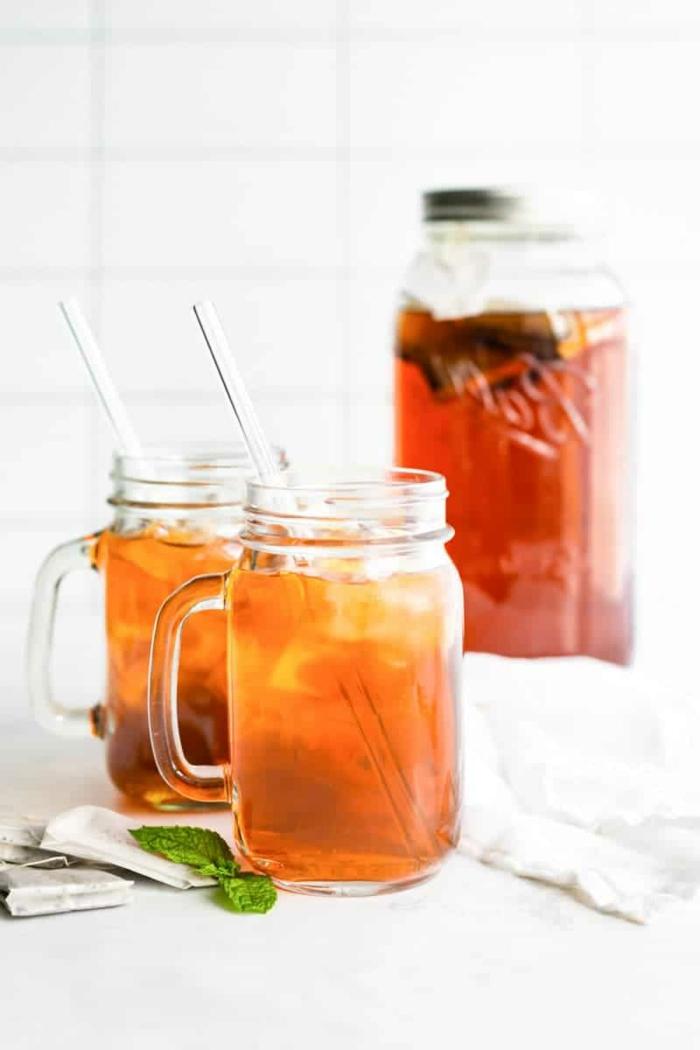 pfirsich eistee selber machen ohne zucker zwei gläser mit orangem getränk ice tea und strphhalmen