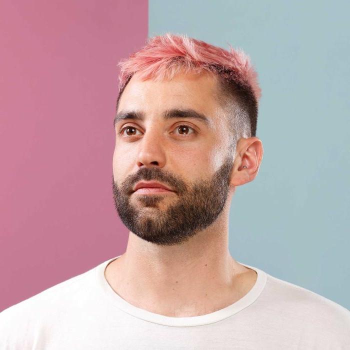 pinke haare undercut haarschnitt männerfrisuren kurz mit bart weißes t shirt pink blauer hintergrund