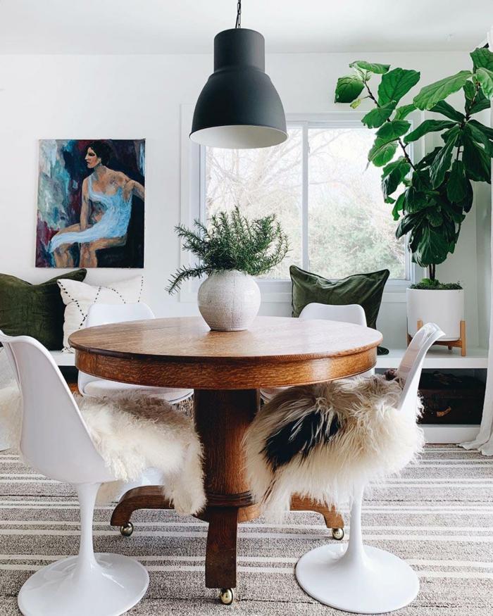 runder tisch aus holz weiße stühle modern artistisches gemälde an die wand große grüne deko pflanze hyggelig wohnen ideen