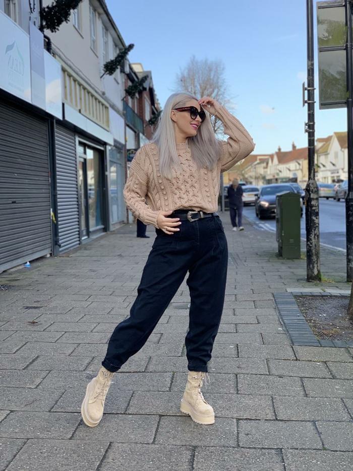 schwarze mom jeans beiges pullover und schuhe dame mit mittellangen blonden haaren schwarze sonnenbrillen