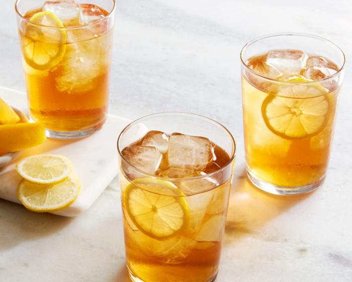 schwarzer tee eistee selber machen rezept ein glas mit geschnittenen zitronen scheiben