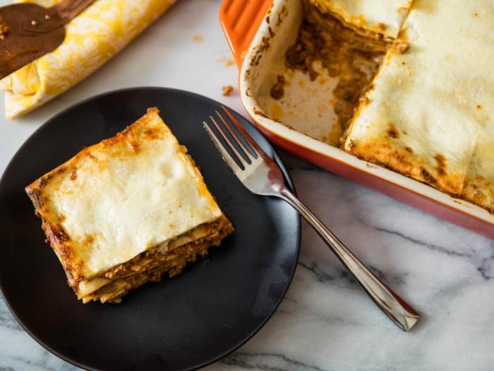 schwarzer teller mit einer vegetarischen lasagne mit käse eine gabel lasagne selber machen rezept