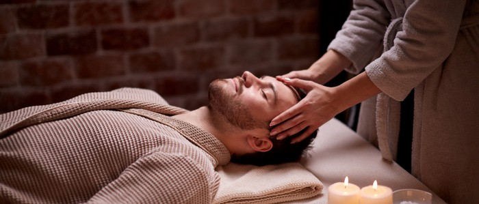 man getting face massage in spa beauty salon