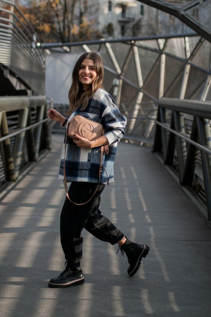 street style inspiration doc martens schuhe schwarze wide leg jeans damen beige handtasche kariertes oversized hemd dame mit langen haaren