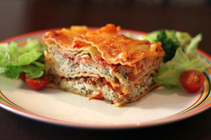 teller mit einem stück lasagne mit spinat und tomaten kleine geschnittene tomaten und salat