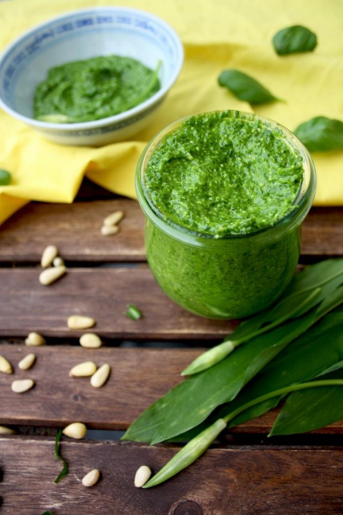 tisch aus holz ein glas mit bärlauch mit olivenöl vegan kochen sonnenblumenkerne eine gelbe decke bärlauch dip
