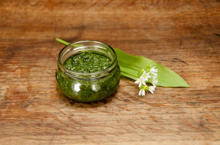tisch aus holz grüne bärlauch blätter ein glas mit grünem bärlauch pesto bärlauch dip