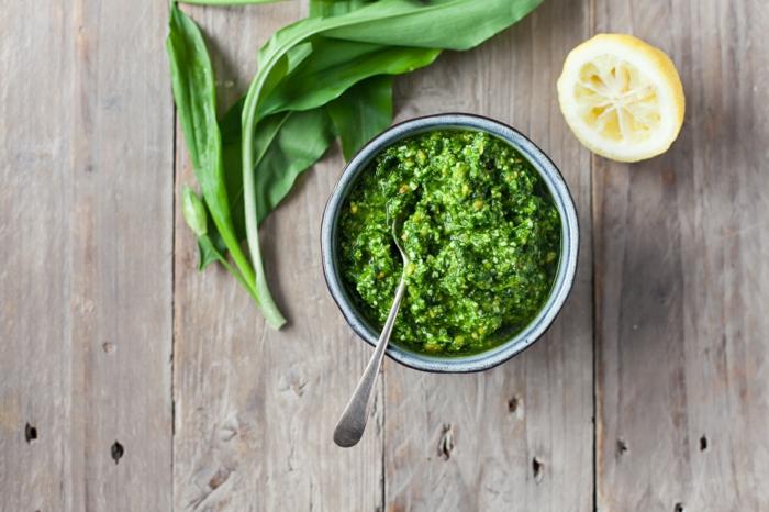 tisch aus holz zitrone grüe blätter ein löffel rezept für bärlauchpesto
