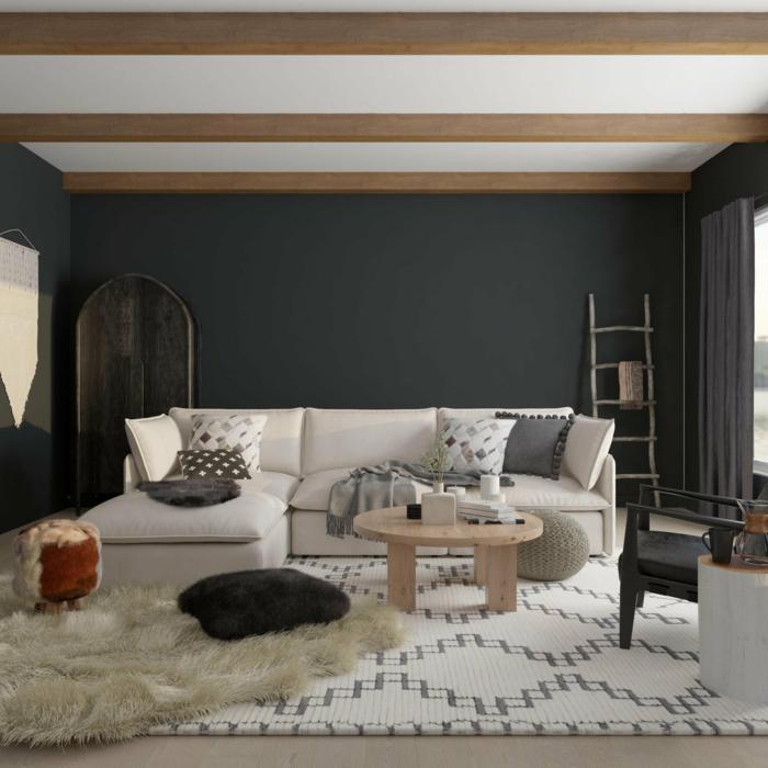 weiße decke mit holzbalken sehr dunkle wand weißer ecksofa und teppich gemütliches wohnzimmer einrichten was ist hyyge einrichtung