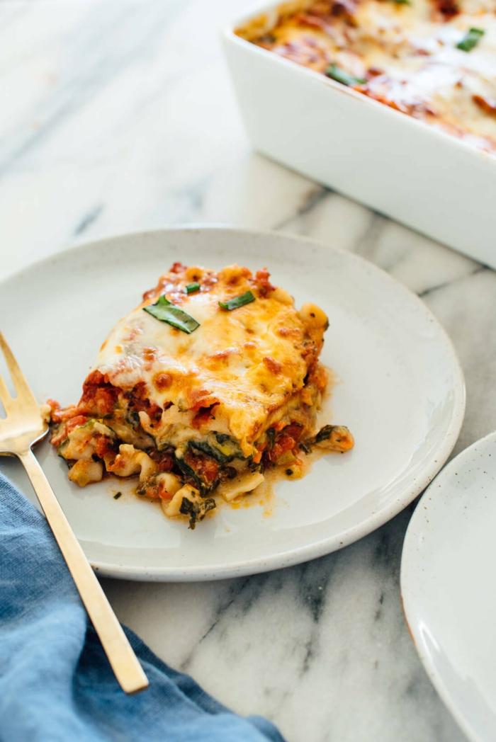 weißer teller lasagne mit tomaten soße faschiertes und käse eine gabel lasagne vegan
