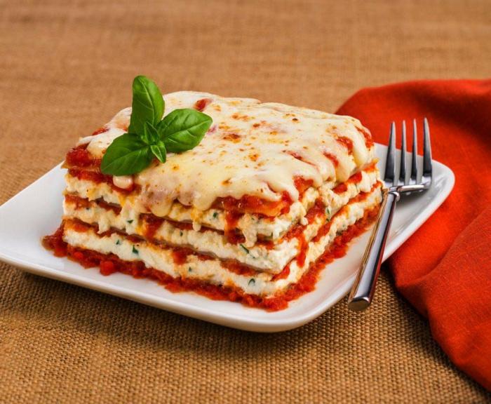 weißer teller mit lasagne bolognesse mit tomatensoße und bailikum eine gabel