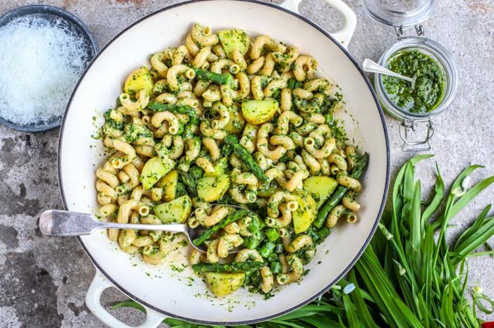 weißer teller mit pasta mit grünem bärlauch pesto ein löffel grüne bärlauch blätter