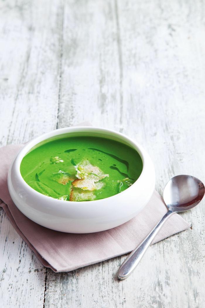 weißer tisch und ein löffel eine weiße shüssel mit grüner suppe mit bärlauch
