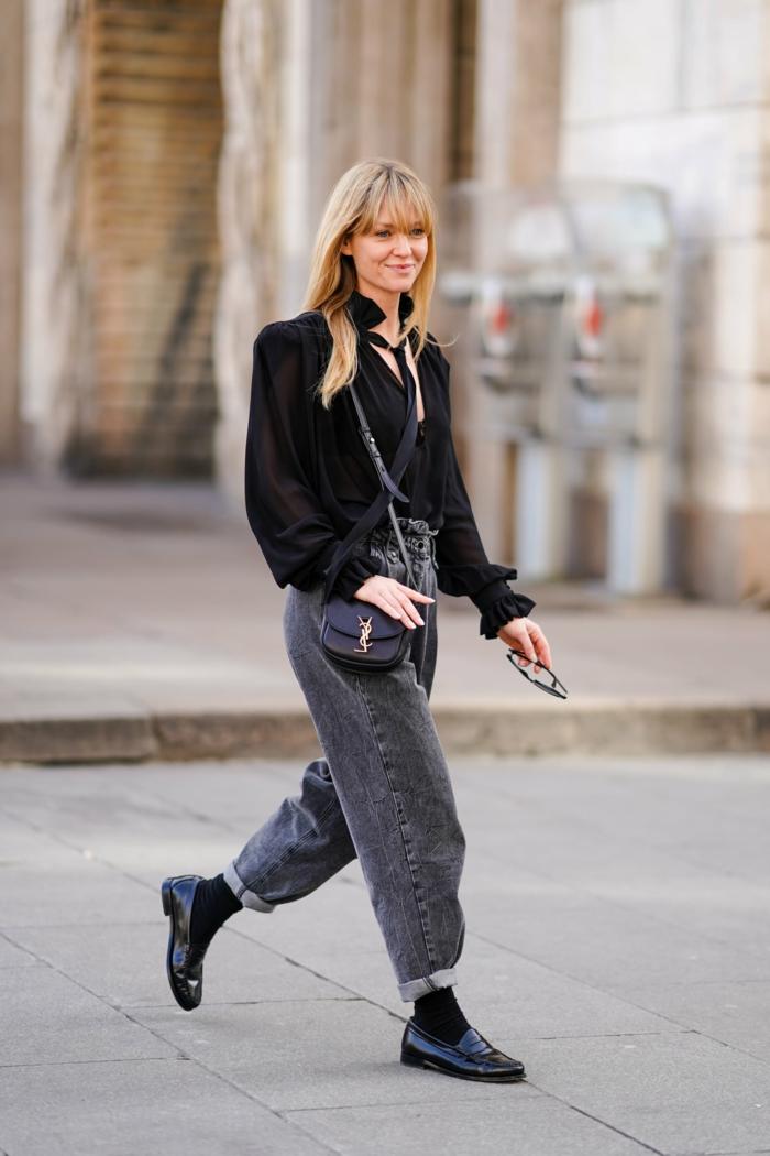 weite schwarze mom jeans lässige schwarze bluse und schuhe dame mit blonden haaren mit pony