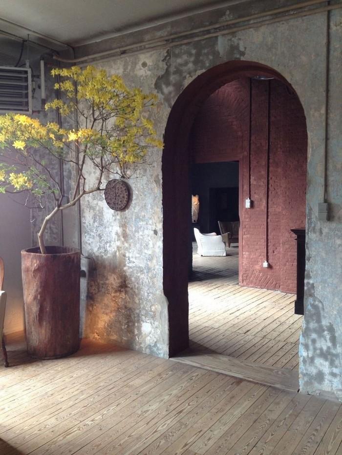 wohnzimmer japanischer stil wabi sabi interior japanische einrochtung japanische inneneinrichtung wohnzimmer mit bogen pflanze in blumentopf aus stein graue wände holzboden