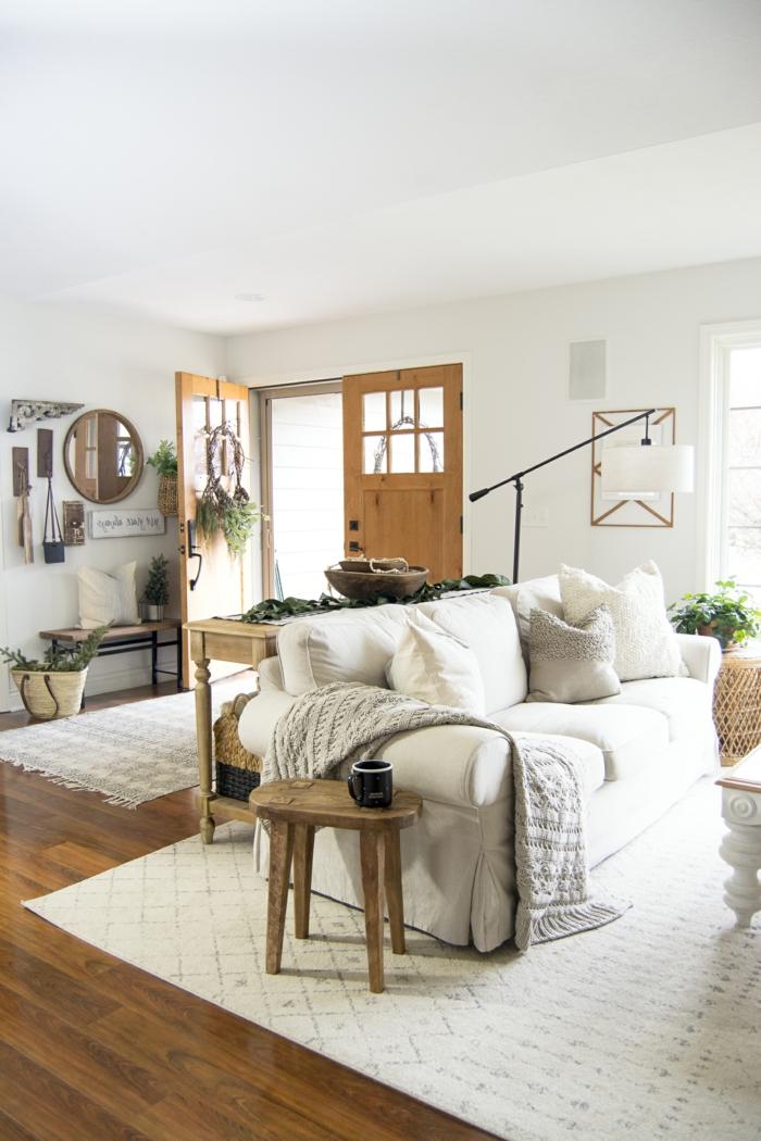 wohnzimmer skandinavischer stil bode und tür aus holz weißes sofa mit vielen kissen hygge style einrichtung