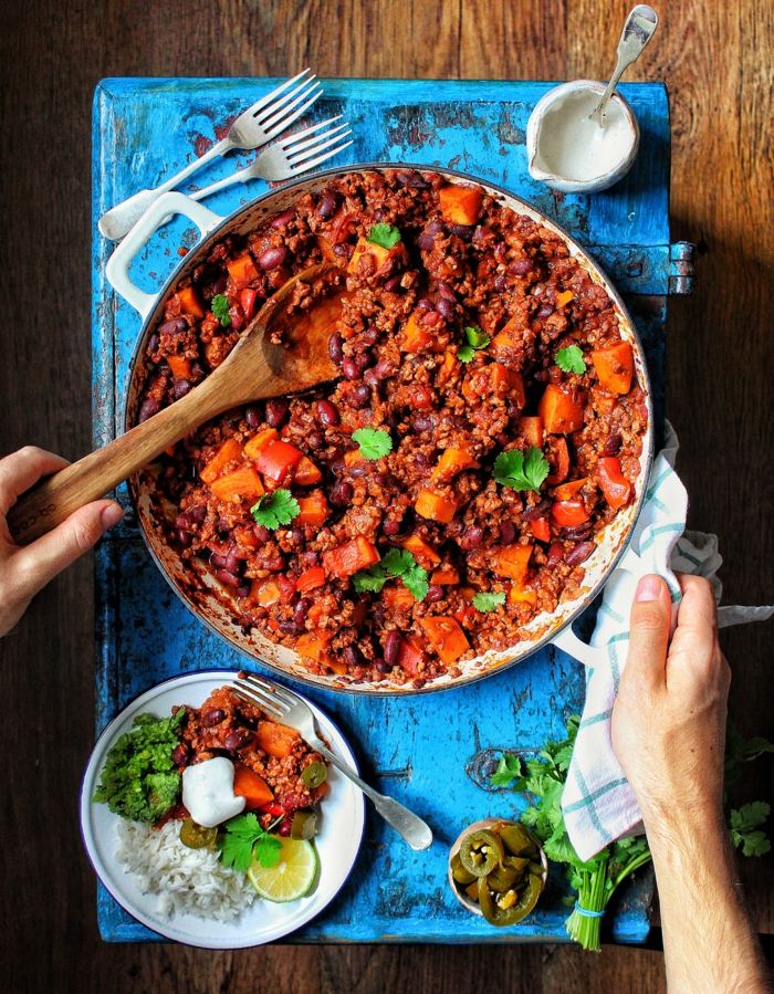 zwei hände chili con carne rezept einfach ein läffel aus holz gericht mit mais chili paprika kreuczkümmel und zwiebeln