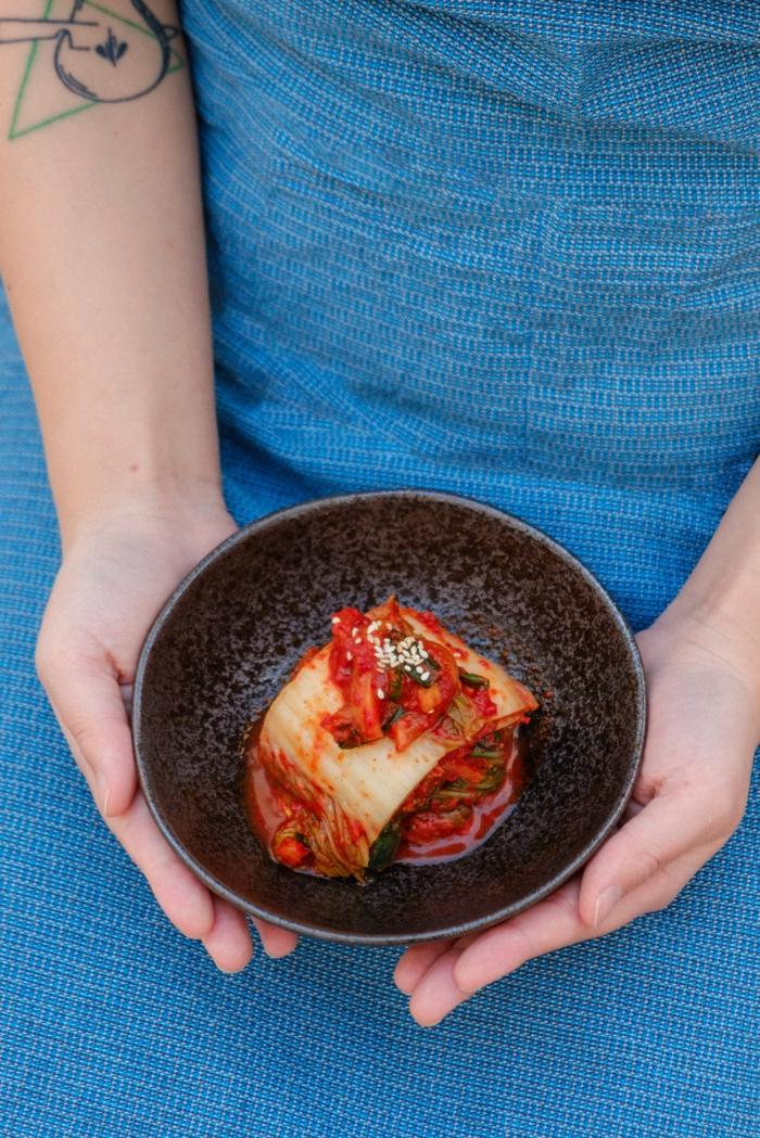 zwei hände einer frau mit tattoo ein kleiner teller mit lasagne mit tomaten soße und faschiertes