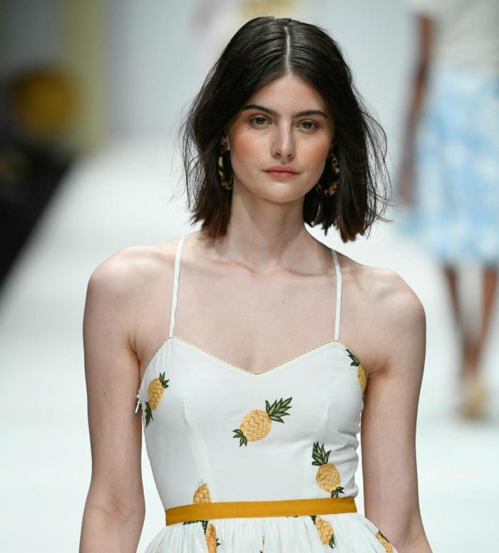 choppy bob haarschnitt mit mittelscheitel model im weißen kleid fashion week fashion show kurze schwarze haare