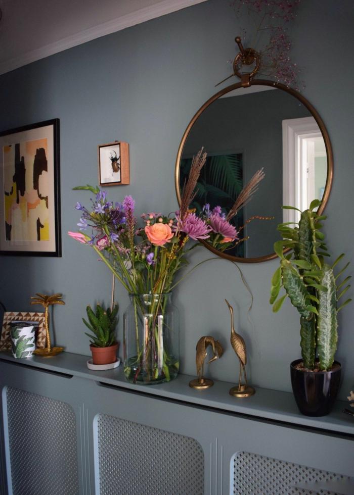 dekoration mit vielen blumen und pflanzen wandfarbe blau flur gestalten wände kleiner runder wandspiegel innenausstattung inspiration