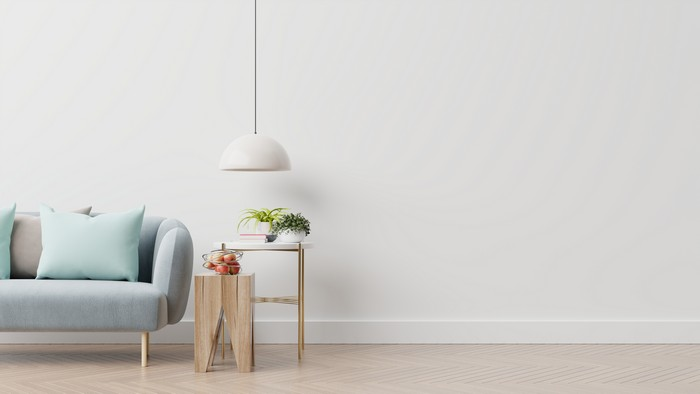 empty living room with blue sofa, plants and table on empty white wall background.