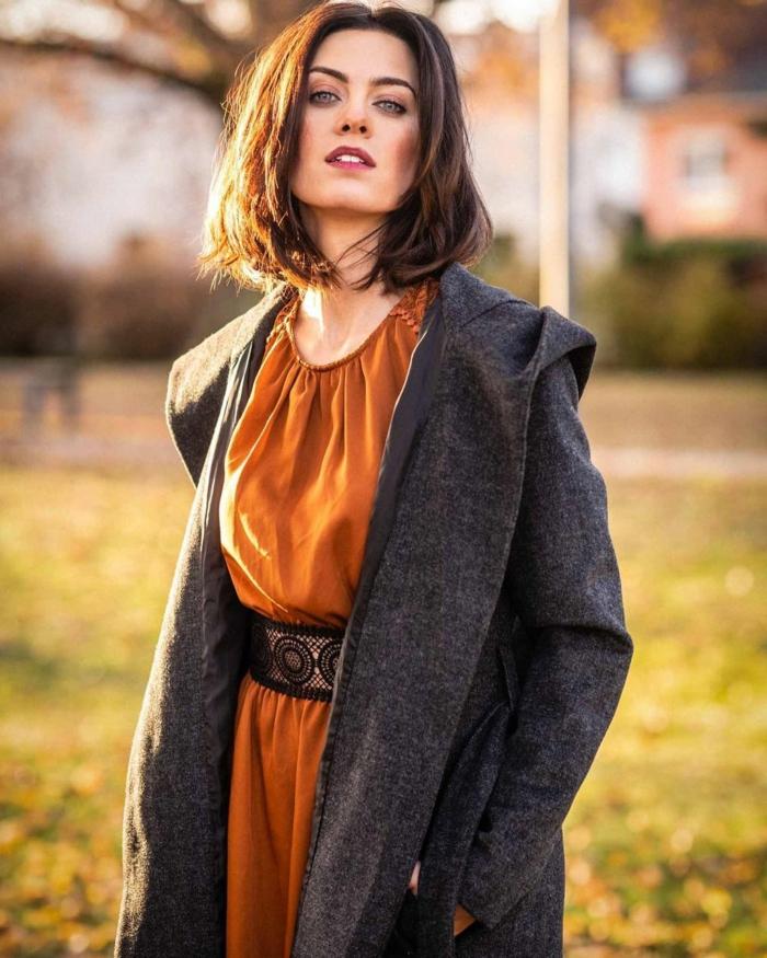 fashion shoot im park herbst outfit grauer mantel ocker kleid dame mit braunen haaren kurzhaarschnitte choppy bob 2021