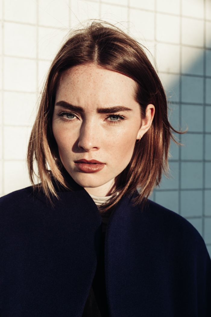 fashion shoot model mit braunen kurzen haaren schön geschminktes gesicht angezogen im schwarzen mantel raffinierte bob frisuren