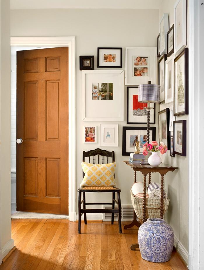 flur gestalten wände mit vielen bildern und fotos vintage stuhl aus holz kleiner tisch blau weiße vase dekoration inspiration eingangsbereich