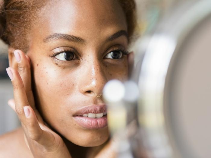 frau schaut in einem spiegel goldenere nasenring wichtige infos für die hautpflege hausmittel gegen pickel