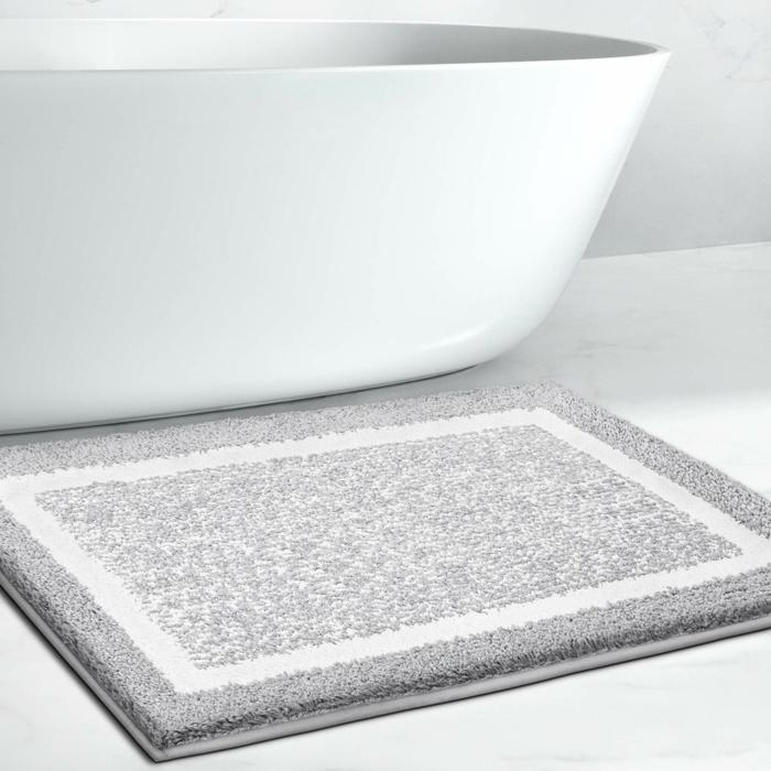 freistehende badewanne ein kleiner grauer teppich