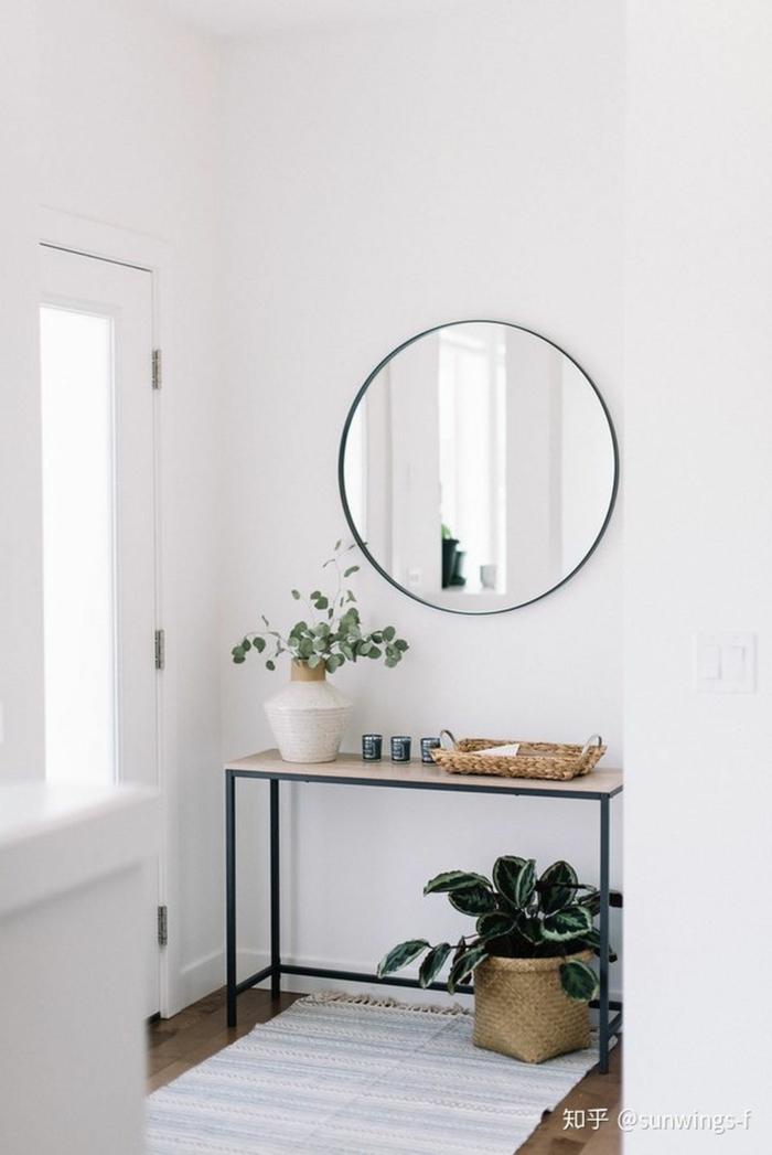 großer runder spiegel an de wand kleiner tisch aus holz mit matallbeinen dekorative grüne pflanzen kleinen flur gestalten inspiration