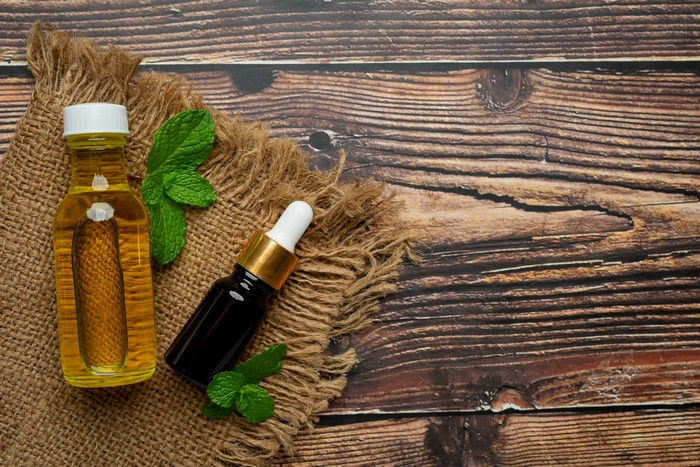 essential oil of peppermint in bottle with fresh green peppermin