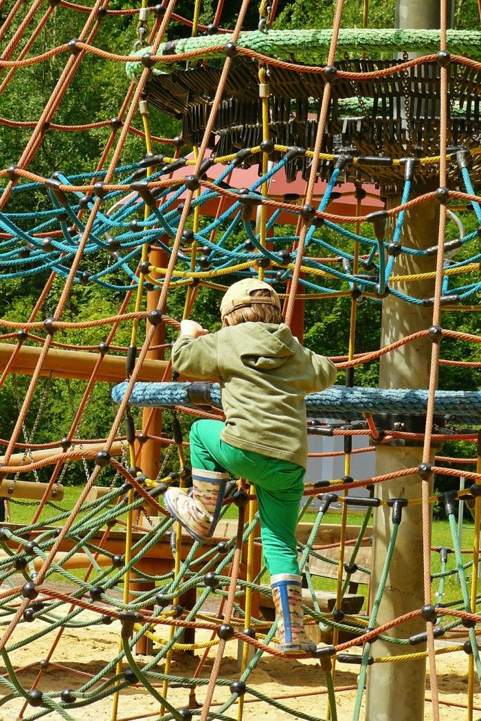indoor klettergerüst vorteie kind spielt auf einem spielplatz mit klettergerüst
