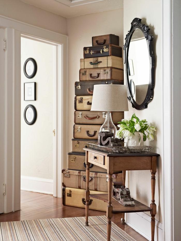 konsolentisch aus holz mit einer schublade vintage spiegel rund aufeinander gelegte alte koffer originelle deko ideen flur gestaln inspiration