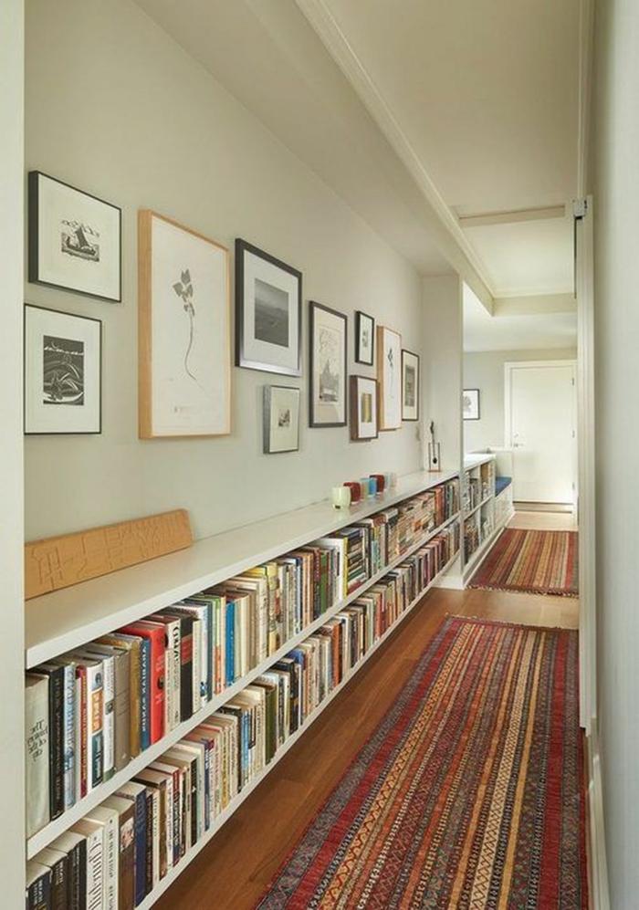 langer großer regal mit vielen büchern bunter teppich kleine und große bilder an die wand eingangsbereich gestalten modern