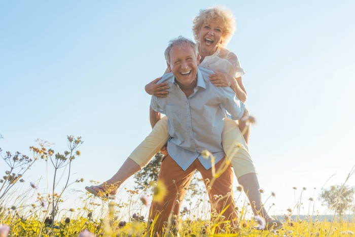 happy senior man laughing while carrying his partner on his back in the countryside