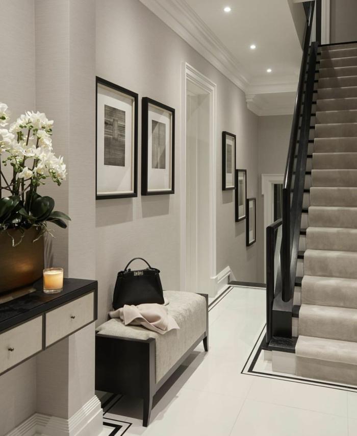 luxuriöser eingangsbreich minimalistische innenausstattung schwarz weiße fotografien dekoration weiße blumen