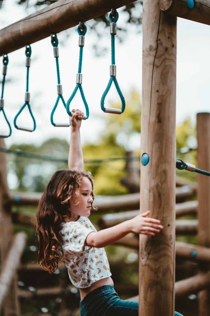 mädchen spielt auf einem klettergerüst indoor klettergerüst physische und geistige entwicklung fördern