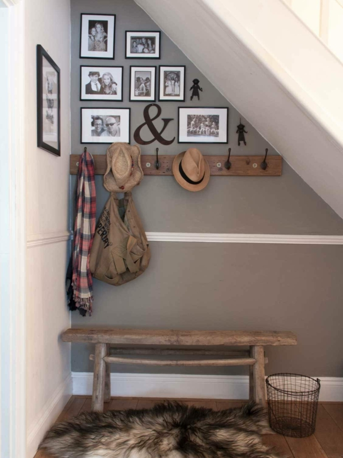 platz unter der treppe nutzen graue wand dekoriert mit fotos vintage bank aus holz flauschiger teppich flur gestalten wände