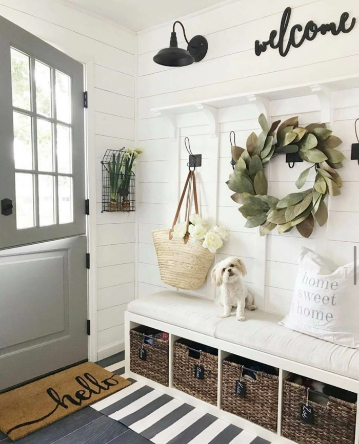 rustikaler stil inneneinrichtung deko grüner kranz weiße wände schwarze lampe weidenkörbe moderner interior design kleiner hund schmalen flur gestalten