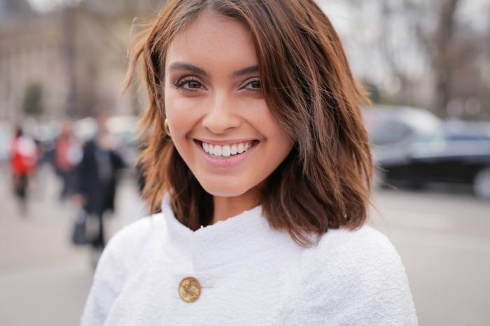 street style paris fashion week dame im weißen mantel kurze braune haare trendfrisuren bob 2021 inspo