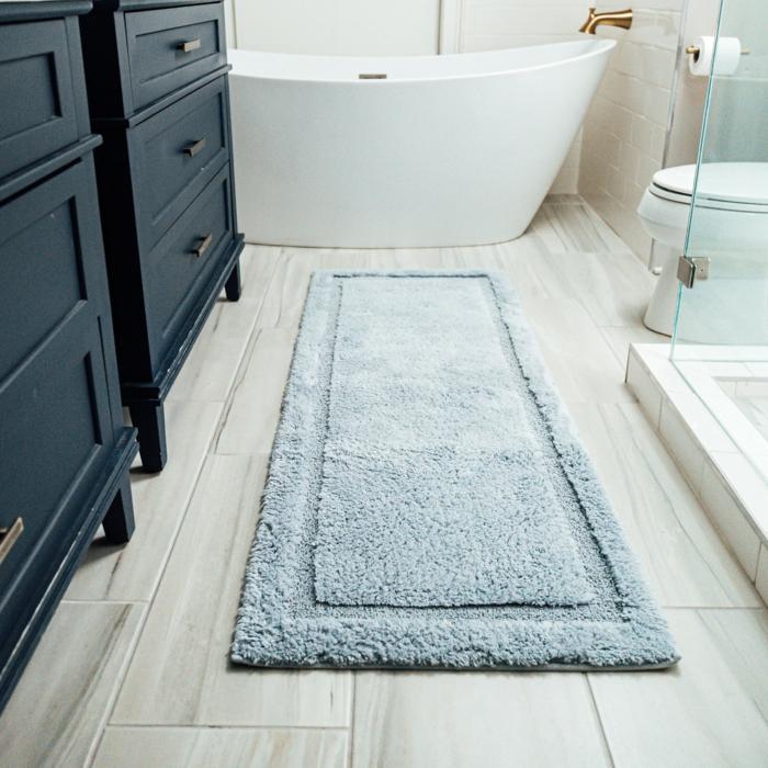 tipps bei der auswahl eines badezimmerteppichs eine weiße freistehende badewanne