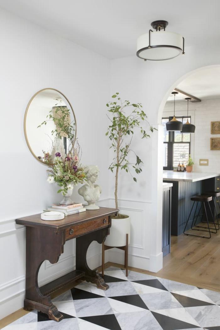 vintage tisch aus holz mit schrank großer runder spiegel dekoration mit pflanzen weiße schwarze fliesen flur gestalten