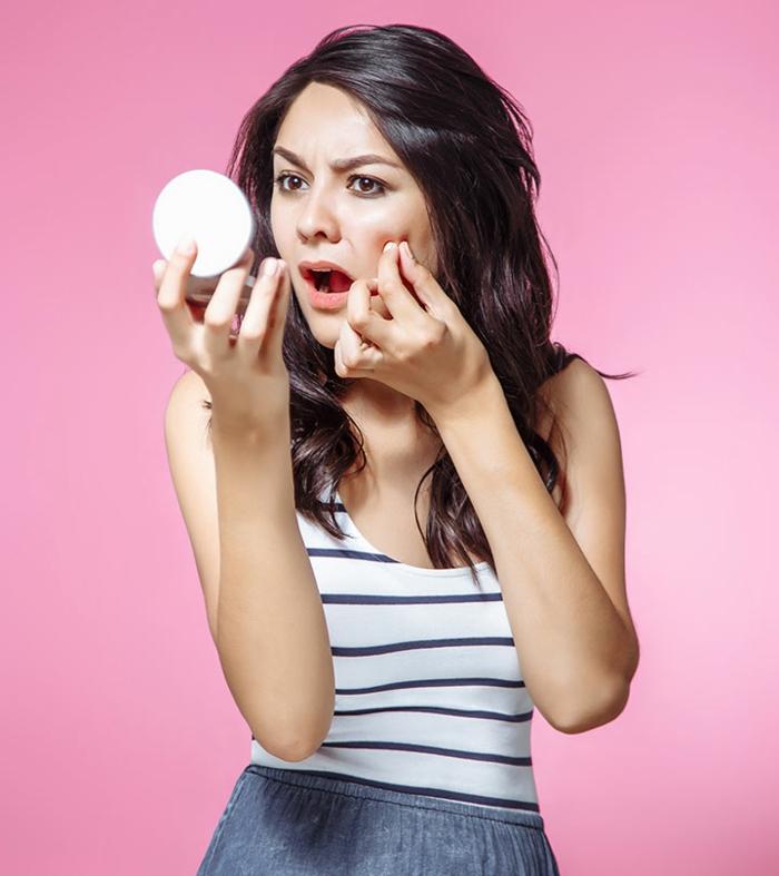 was hilft gegen mitesser junge frau schaut ihr gesicht im spiegel pickel schnell loswerden